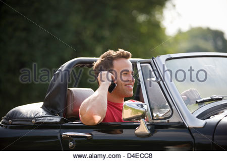 A young man sitting in a black sports car holding a mobile phone - Stock Photo