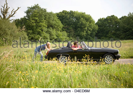 A young woman pushing a black sports car, a man in the driving seat - Stock Photo