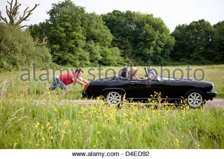 A young man pushing a black sports car, a woman in the driving seat - Stock Photo