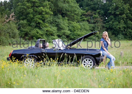 A young woman sitting on her broken down car speaking on a mobile phone - Stock Photo