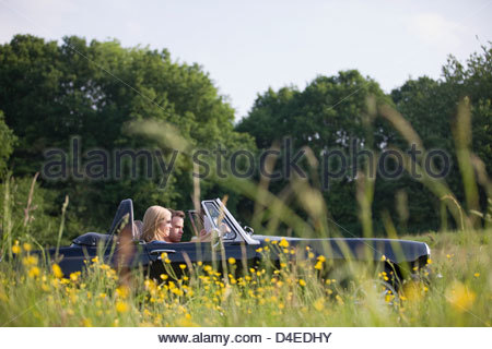 A young couple driving in the countryside, man looking at a road map - Stock Photo