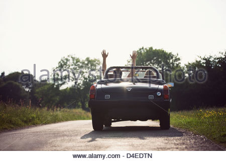 A young couple driving in a convertible black sports car, man with his arms in the air - Stock Photo