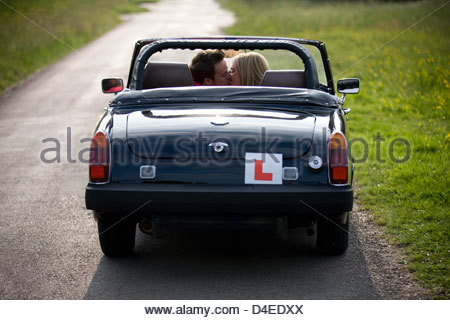 A young couple in a black sports car kissing, rear view - Stock Photo