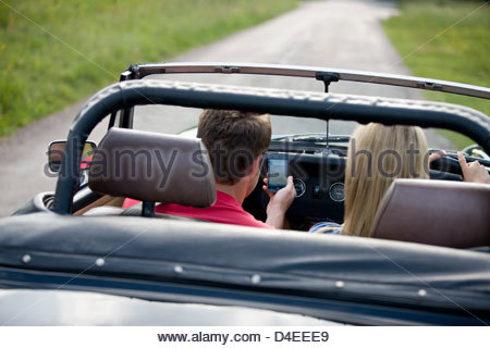 A young couple driving in the countryside, man looking navigating using a smartphone - Stock Photo