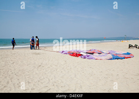 Concept, getting ready for paragliding over the sandy shoreline on beach parachute laid flat on ground - Stock Photo
