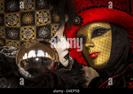 Two women dressed up for the Carnival in Venice holds a metal ball in which St Marco and people are reflected, Italy - Stock Photo