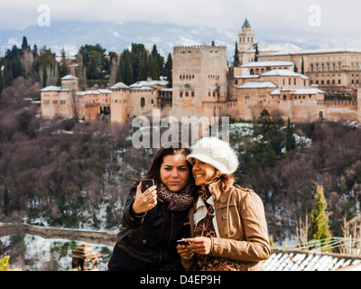 Two female tourist friends taking a selfie with a cellphone camera and snowcapped Alhambra palace in Background. - Stock Photo