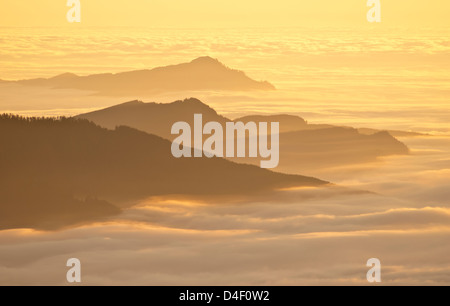 Aerial view of mountaintops over clouds at sunset - Stock Photo