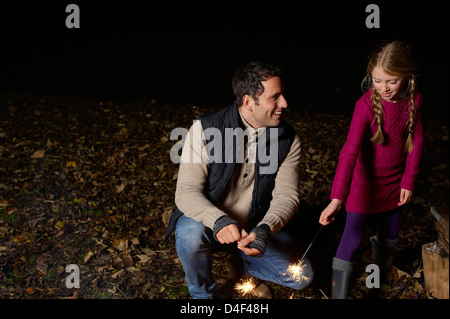 Father and daughter playing with sparklers - Stock Photo