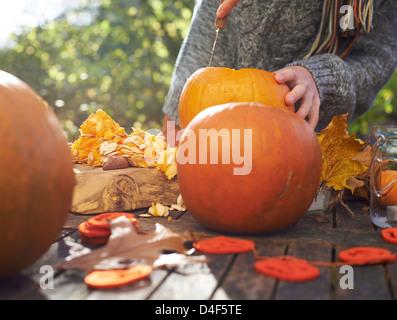 Teenage boy carving pumpkins outdoors - Stock Photo