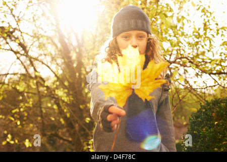 Girl holding autumn leaf outdoors - Stock Photo