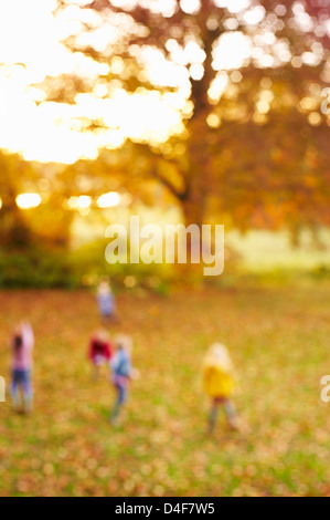 Blurred view of children in field - Stock Photo