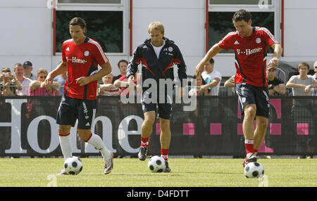 FC Bayern Munich's new head coach Juergen Klinsmann (C)and his players Mark van Bommel (R) and Daniel van Buyten - Stock Photo