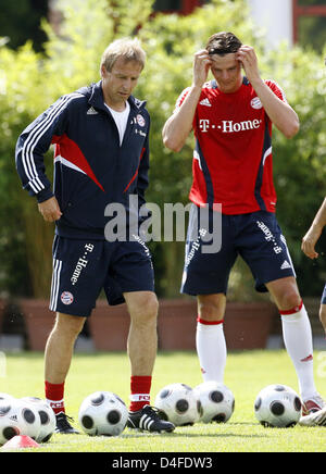 FC Bayern Munich's new head coach Juergen Klinsmann (L) and Daniel van Buyten are pictured during the kick-off training - Stock Photo