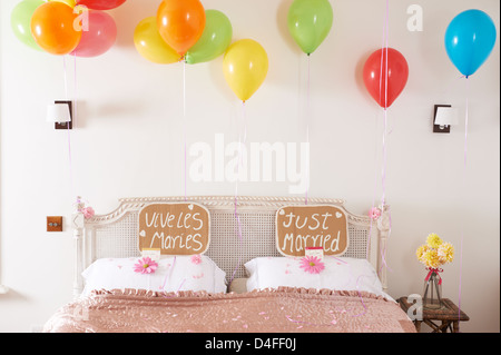Decorated marriage bed with balloons and signs - Stock Photo