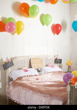 Colorful balloons over marriage bed - Stock Photo