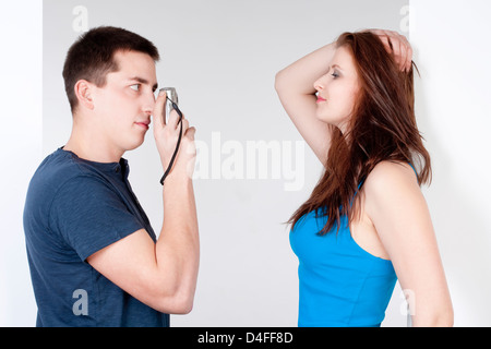 young man taking pictures of his girlfriend - Stock Photo