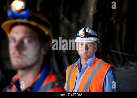 Businessman and worker standing in tunnel - Stock Photo