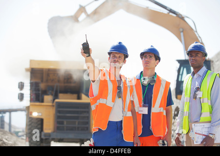 Workers and businessman standing in quarry - Stock Photo