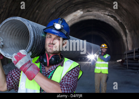 Workers carrying long pipe in tunnel - Stock Photo