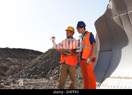 Workers talking by machinery in quarry - Stock Photo