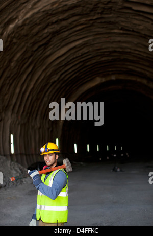 Worker holding sledgehammer in tunnel - Stock Photo