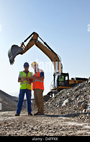 Workers talking by digger in quarry - Stock Photo
