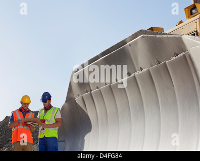 Workers reading blueprints by digger in quarry - Stock Photo