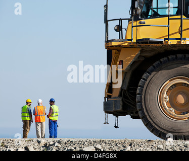 Workers talking with machinery in quarry - Stock Photo