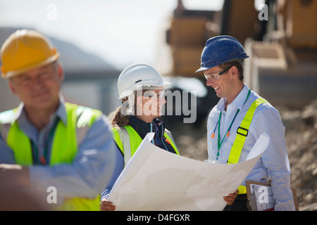 Business people reading blueprints in quarry - Stock Photo