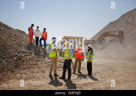 Business people and workers talking in quarry - Stock Photo