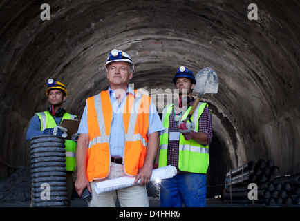 Businessman and workers standing in tunnel - Stock Photo