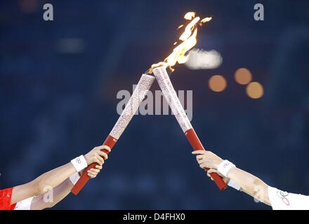 Torch bearers hand-over the flame during the Opening Ceremony of the Beijing 2008 Olympic Games at the National - Stock Photo
