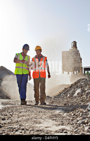 Workers talking in quarry - Stock Photo