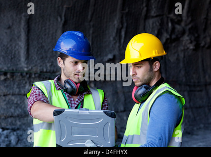 Workers using laptop in tunnel - Stock Photo