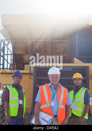 Businessman and workers by machinery on site - Stock Photo