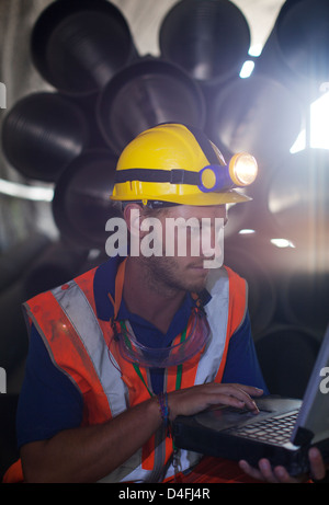 Worker using laptop in tunnel - Stock Photo