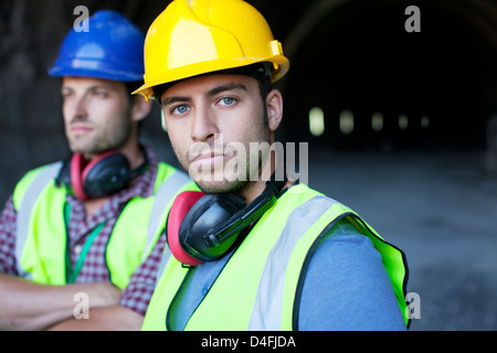 Workers looking out from tunnel - Stock Photo