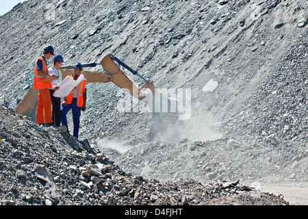 Workers and businessman talking in quarry - Stock Photo