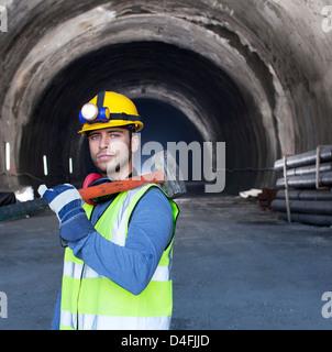 Worker holding sledgehammer in tunnel - Stock Photo