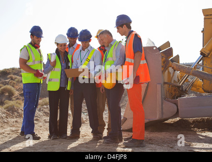 Workers and business people talking on site - Stock Photo