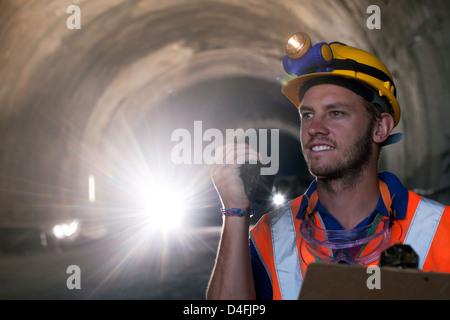 Worker using walkie-talkie in tunnel - Stock Photo