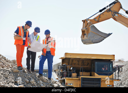 Workers and businessman reading blueprints in quarry - Stock Photo