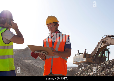 Workers standing in quarry - Stock Photo