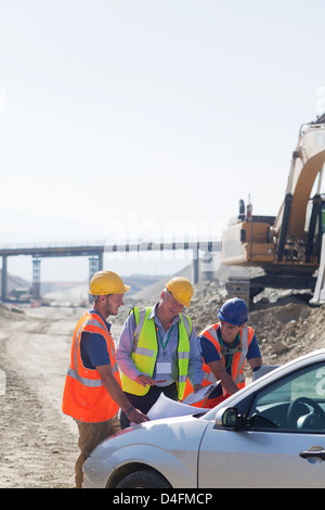 Businessman and workers talking in quarry - Stock Photo