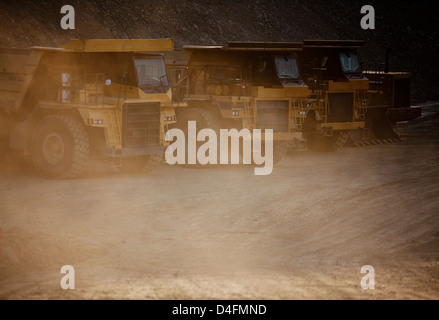 Trucks parked on road in quarry - Stock Photo