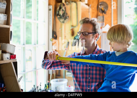 Father and son working in garage - Stock Photo
