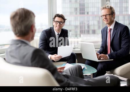 Businessmen talking in office area - Stock Photo