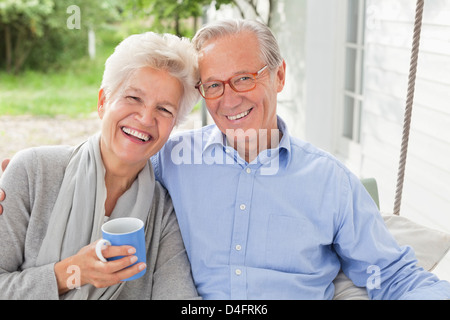 Smiling couple sitting on porch swing - Stock Photo