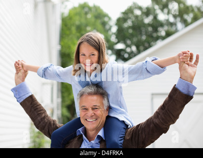 Man carrying granddaughter on shoulders - Stock Photo